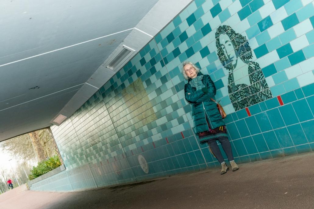 Kunstenares Louise Hessel poseert bij beeltenis Spinoza onder de Spinozabrug.